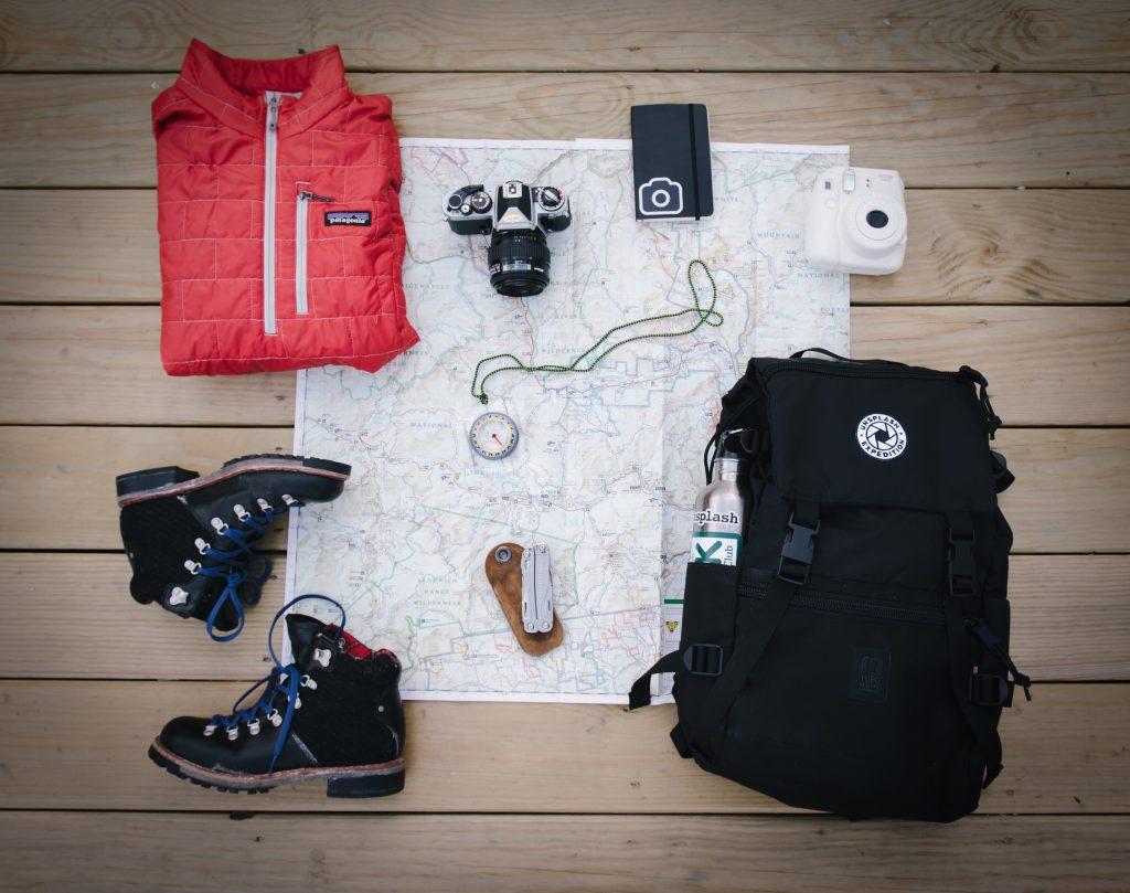 photo de l'interieur d'une valise avec des chaussures de marches, un kway et un appareil photo -Retrouvez nos conseils sur le blog de New York Off Road en fonction des saisons, visites guidées en français de la Grosse Pomme