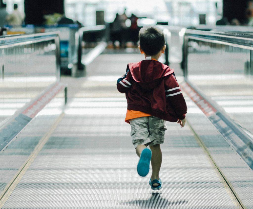 enfant courant dans un aéroport. New York Off Road vous dit tout sur les futures conditions de voyage vers les USA, y compris pour les enfants.